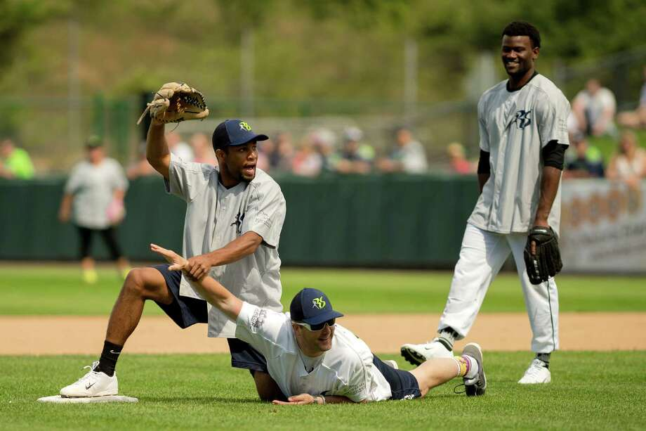 "Golden Tate, left, attempts to ""fix"" a play at second base during the Richard Sherman Celebrity Softball Game Sunday, July 7, 2013, at Cheney Stadium in Tacoma, Wash. The family-friendly event featured a home run derby with a portion of all proceeds going to Blanket Coverage, The Richard Sherman Family Foundation and Homes for Heroes. Photo: JORDAN STEAD, SEATTLEPI.COM / SEATTLEPI.COM"