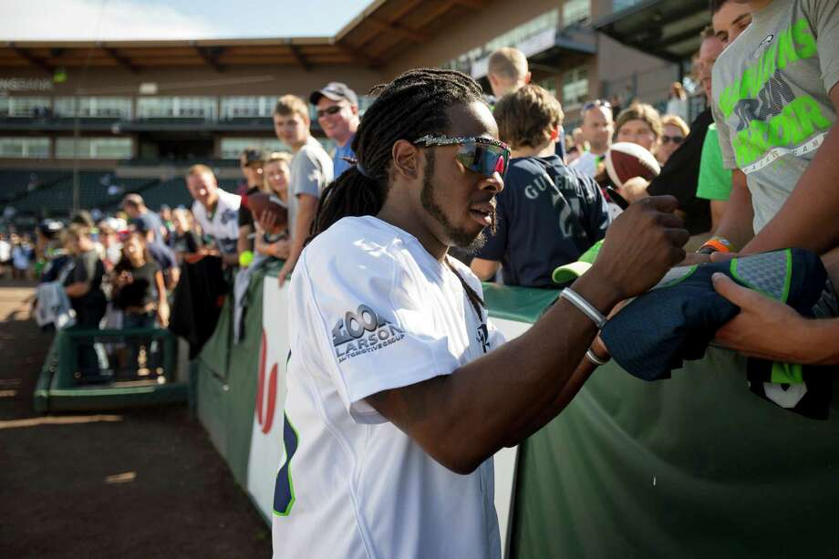 Richard Sherman signs hats and jerseys for fans following the Richard Sherman Celebrity Softball Game Sunday, July 7, 2013, at Cheney Stadium in Tacoma, Wash. The family-friendly event featured a home run derby with a portion of all proceeds going to Blanket Coverage, The Richard Sherman Family Foundation and Homes for Heroes. Photo: JORDAN STEAD, SEATTLEPI.COM / SEATTLEPI.COM
