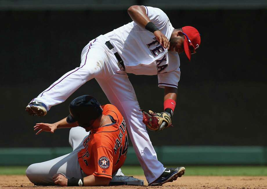 J.D. Martinez is tagged out by Elvis Andrus in a ragged game that saw the Astros have two runners caught stealing and another picked off and that saw two Rangers errors aid a rally. Photo: Ronald Martinez, Staff / 2013 Getty Images