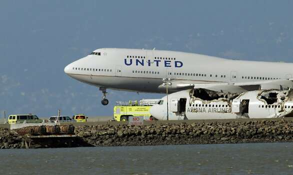 A United Airlines plane lands near the crashed fuselage of Flight 214 while officials from NTSB continued investigating the crash Sunday. San Francisco International Airport, city officials and National Transportation Safety Board members earlier detailed the investigation into the crash of Asiana Flight 214 at a press conference at SFO on Sunday, July 7, 2013, in San Francisco, Calif. Photo: Carlos Avila Gonzalez, The Chronicle