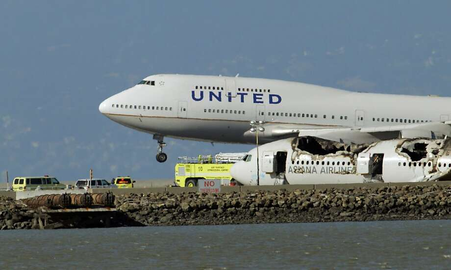 A United Airlines plane takes off near the crashed fuselage of Flight 214 while officials from NTSB continued investigating the crash Sunday. San Francisco International Airport, city officials and National Transportation Safety Board members earlier detailed the investigation into the crash of Asiana Flight 214 at a press conference at SFO on Sunday, July 7, 2013, in San Francisco, Calif. Photo: Carlos Avila Gonzalez, The Chronicle