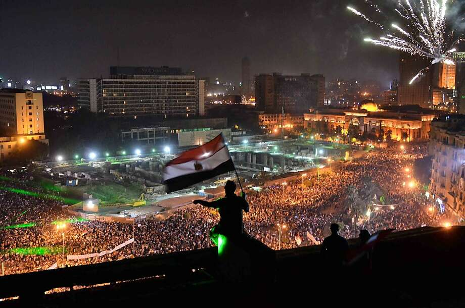 TOPSHOTS Egyptians wave the national flag on a building rooftop on July 7, 2013 as hundreds of thousands flood Egypt's landmark Tahrir square to demontrate against ousted President Mohammed Morsi and in support of the Egyptian Army in Cairo. Opponents of Egypt's first freely elected leader packed streets across the country in their hundreds of thousands on July 7 to show the world his ouster was not a military coup but the reflection of the people's will. Staged two days after Islamist rallies exploded into bloodshed, the protests came as a coalition that backed the military action to overthrow Morsi reportedly agreed to name a technocrat as premier.  AFP PHOTO / MOHAMED EL-SHAHEDMOHAMED EL-SHAHED/AFP/Getty Images Photo: Mohamed El-shahed, AFP/Getty Images