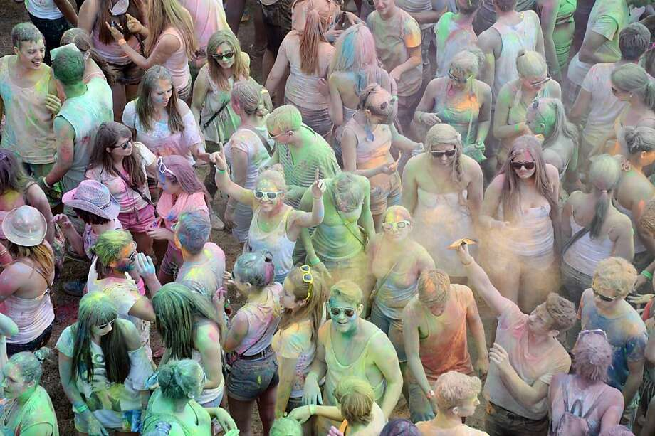TOPSHOTS People throw colorful powder during the Holi Festival of Colours near Karlsruhe, southern Germany, on July 7, 2013. Originally, the festival was celebrated in north India by throwing colorful powers onto each other to celebrate spring and to drive away evil spirits. AFP PHOTO / ULI DECK / GERMANY OUTULI DECK/AFP/Getty Images Photo: Uli Deck, AFP/Getty Images