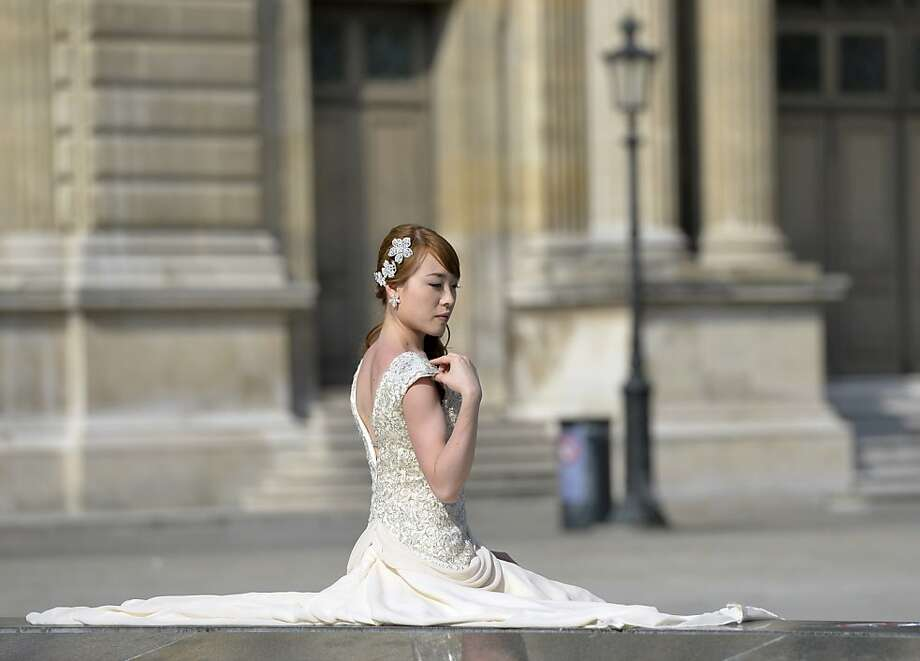 A newly-married woman poses near the Louvre museum on July 7, 2013 in Paris.     TOPSHOTS/AFP PHOTO/MIGUEL MEDINAMIGUEL MEDINA/AFP/Getty Images Photo: Miguel Medina, AFP/Getty Images