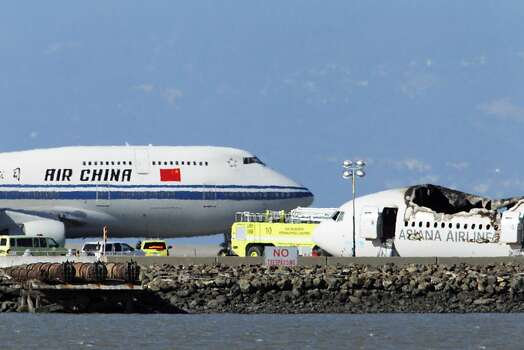 An Air China plane taxis for take off on runway 28R near the debris from Flight 214 while officials from NTSB continued investigating the crash Sunday. San Francisco International Airport, city officials and National Transportation Safety Board members earlier detailed the investigation into the crash of Asiana Flight 214 at a press conference at SFO on Sunday, July 7, 2013, in San Francisco, Calif. Photo: Carlos Avila Gonzalez, The Chronicle