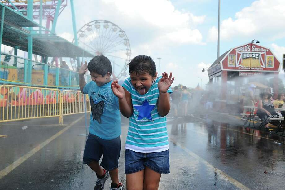 Fair-goers enjoy a spray from a power washer while enjoying a hot afternoon at the final day of the State Fair Meadowlands, Sunday, July 7, 2013. (AP Photo/The Record, Tyson Trish) Photo: Tyson Trish, Associated Press