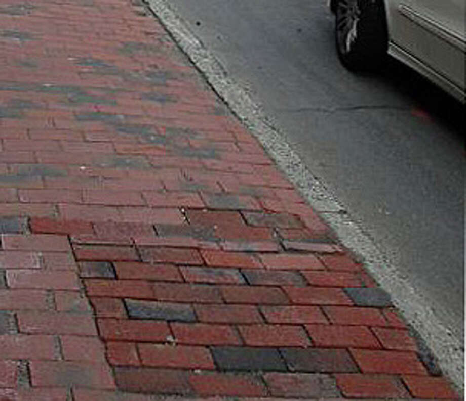 Tree were cut down along Main Street last year  -- and the sites filled in as here with newer, darker bricks -- without proper permission, according to the town's Tree Board, whose members are frustrated over lack of progress in replacing the trees. Photo: File Photo / Westport News