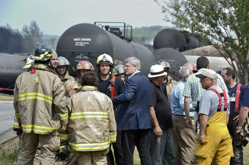 Prime Minister Harper, center, talks with firefighters Sunday, July 7, 2013, in Lac Megantic, Quebec