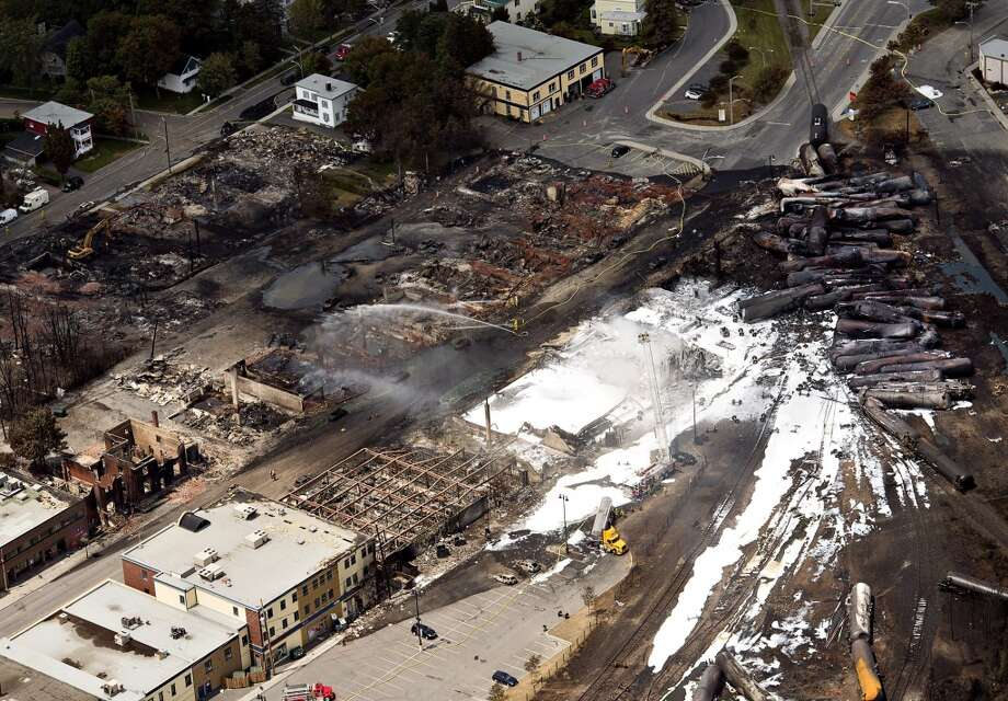 The downtown core lays in ruins as fire fighters continue to water smoldering rubble Sunday, July 7, 2013 in Lac Megantic, Quebec.  A runaway train derailed  Saturday igniting tanker cars carrying crude oil. (AP Photo/THE CANADIAN PRESS,Ryan Remiorz) Photo: Associated Press