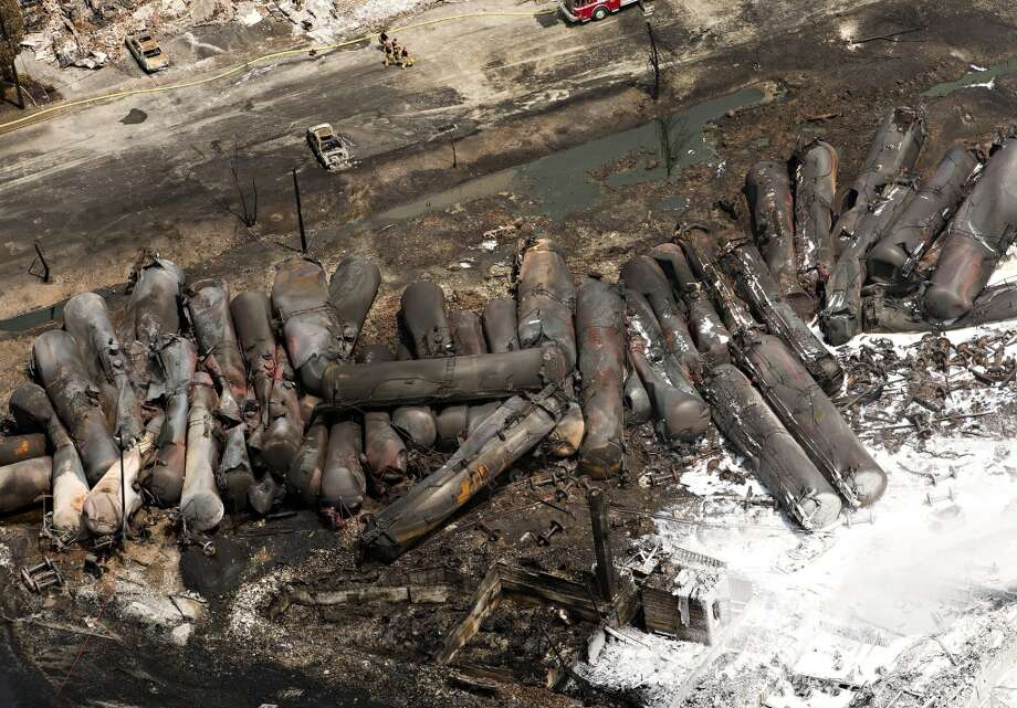 The remains of tanker cars lie burnt out in the downtown core Sunday, July 7, 2013, in Lac Megantic, Quebec.   A runaway train derailed  Saturday igniting tanker cars carrying crude oil and devastated the town. (AP Photo/THE CANADIAN PRESS,Ryan Remiorz) Photo: Associated Press