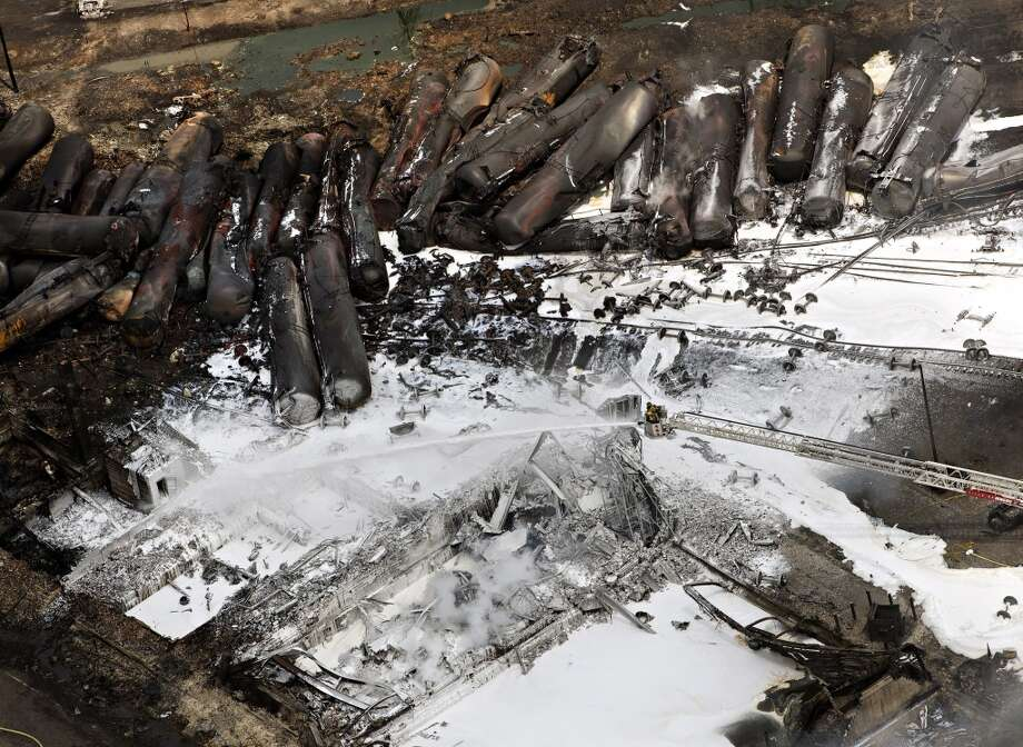 Burnt out oil tank cars  and the destroyed downtown core lays in ruins as firefighters continue to water smouldering rubble Sunday, July 7, 2013, in Lac Megantic, Quebec.  A runaway train derailed igniting tanker cars carrying crude oil on Saturday.  (AP Photo/ THE CANADIAN PRESS,Ryan Remiorz) Photo: Associated Press