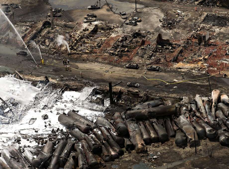 The downtown core lays in ruins as fire fighters continue to water smoldering rubble Sunday, July 7, 2013 in Lac Megantic, Quebec.    A runaway train derailed  Saturday igniting tanker cars carrying crude oil. (AP Photo/THE CANADIAN PRESS,Ryan Remiorz) Photo: Ryan Remiorz, Associated Press