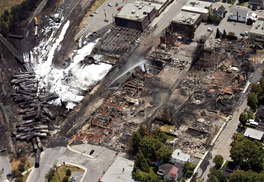 The downtown core lays in ruins as fire fighters continue to water smoldering rubble Sunday, July 7, 2013, in Lac Megantic, Quebec.    A runaway train derailed  Saturday igniting tanker cars carrying crude oil. (AP Photo/THE CANADIAN PRESS,Ryan Remiorz) Photo: Associated Press