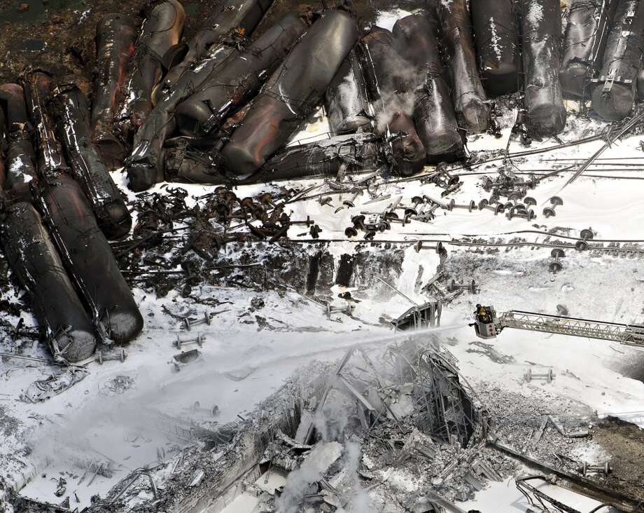 Fire fighters continue to water smoldering rubble  Sunday, July 7, 2013 in Lac Megantic, Quebec.  A runaway train derailed  Saturday igniting tanker cars carrying crude oil. (AP Photo/THE CANADIAN PRESS,Ryan Remiorz) Photo: Associated Press