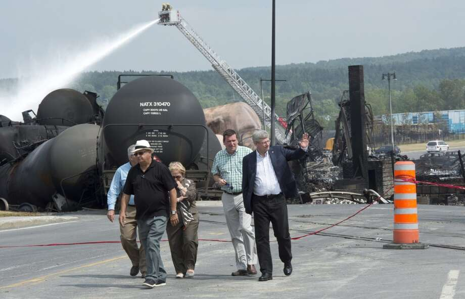 Prime Minister Stepen Harperwaves to people as he visits the site Sunday, July 7, 2013 in Lac Megantic, Quebec, where a runaway train derailed Saturday.   Tanker cars carrying oil exploded after the derailment and destroyed the business district in Lac Megantic.  (AP Photo/The Canadian Press, Paul Chiasson) Photo: Associated Press