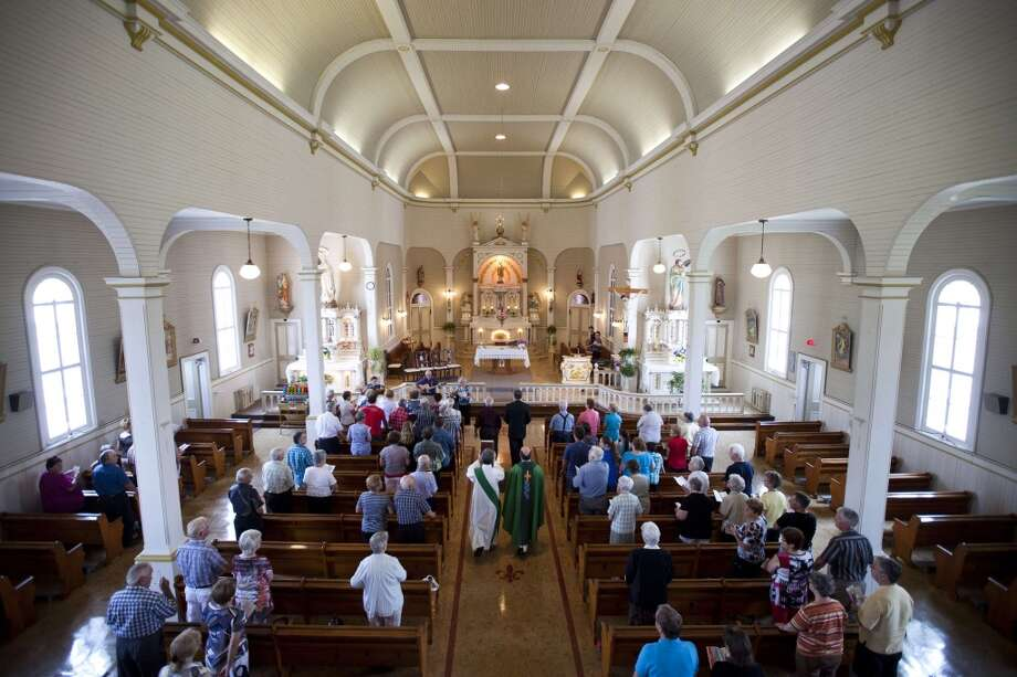 People attend Mass to pray for the victims of a train derailment and subsequent explosion and fire at a church in the village of Sainte-Cécile-de-Whitton, a few kilometres from Lac-Megantic in Canada's Quebec province July 7, 2013. Now scores of people -- perhaps as many as 80 -- are missing. Rescuers cautiously entered the charred debris Sunday, more than 24 hours after the spectacular crash that saw flames shoot into the sky and burn into the night. The accident and resulting huge fireball forced 2,000 people from their homes. Witnesses reported up to six explosions after the train derailed at about 1:20 am (0520 GMT Saturday) in Lac-Megantic.  Four bodies were found Sunday morning, bringing the official death toll from the disaster to five.   AFP PHOTO /  François Laplante-DelagraveFrançois Laplante-Delagrave/AFP/Getty Images Photo: AFP/Getty Images