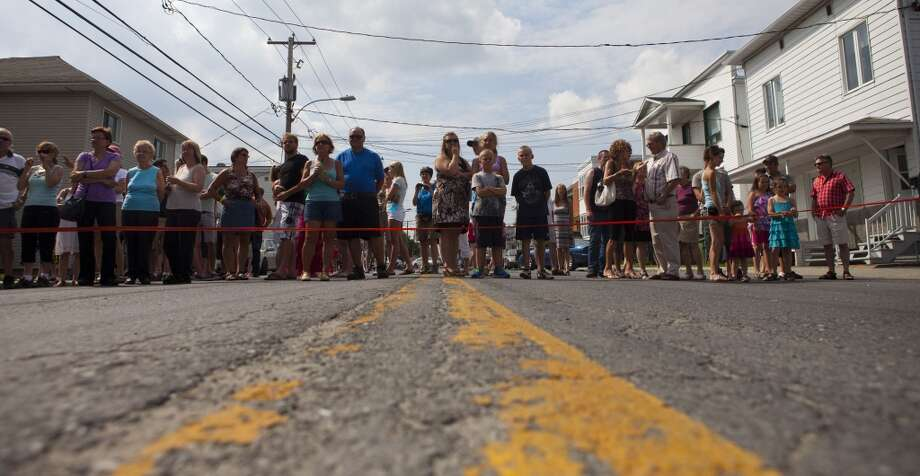 People watch relief operations on July 7, 2013 in Lac-Megantic, Quebec, Canada, one day after a train derailment and subsequent explosion and fire.   Five bodies of victims have been recovered in Quebec from the catastrophic derailment of an oil-laden cargo train, but 40 people are missing and the toll is expected to rise, Canadian officials said.      AFP PHOTO /  François Laplante-DelagraveFrançois Laplante-Delagrave/AFP/Getty Images Photo: AFP/Getty Images