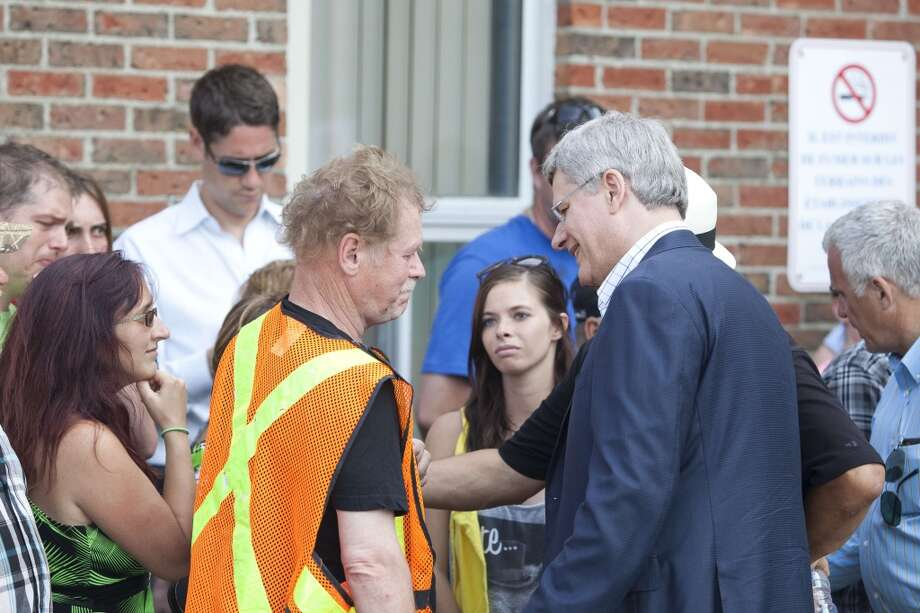 Canadian Prime Minister Stephen Harper greets families following a press conference in the emergency camp set up at Lac-Mégantic high school on July 7, 2013 in Lac-Megantic, Quebec, Canada, one day after a train derailment and subsequent explosion and fire.   Five bodies of victims have been recovered in Quebec from the catastrophic derailment of an oil-laden cargo train, but 40 people are missing and the toll is expected to rise, Canadian officials said.      AFP PHOTO /  François Laplante-DelagraveFrançois Laplante-Delagrave/AFP/Getty Images Photo: AFP/Getty Images