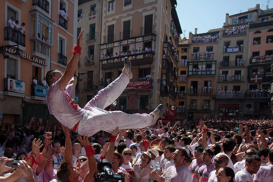 Revellers celebrate during the opening day or 'Chupinazo', of the San Fermin Running of the Bulls fiesta on July 6, 2013 in Pamplona, Spain. The annual Fiesta de San Fermin, made famous by the 1926 novel of US writer Ernest Hemmingway entitled 'The Sun Also Rises,' involves the running of the bulls through the historic heart of Pamplona, this year for nine days from July 6-14. Photo: Pablo Blazquez Dominguez, Getty Images / 2013 Getty Images