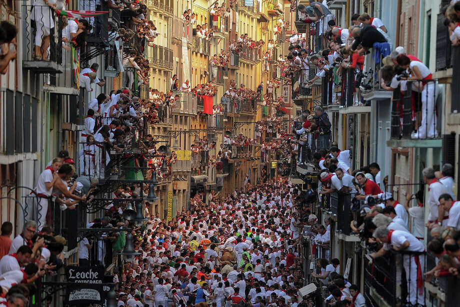 Spaniards standing on balconies watch participants as they run in front of Alcurrucen's bulls during the first bull run of the San Fermin Festival, on July 7, 2013, in Pamplona, northern Spain. The annual Fiesta de San Fermin, made famous by the 1926 novel of US  writer Ernest Hemmingway 'The Sun Also Rises', involves the running of  the bulls through the historic heart of Pamplona, this year for nine  days from July 6-14. Photo: PEDRO ARMESTRE, AFP/Getty Images / 2013 AFP