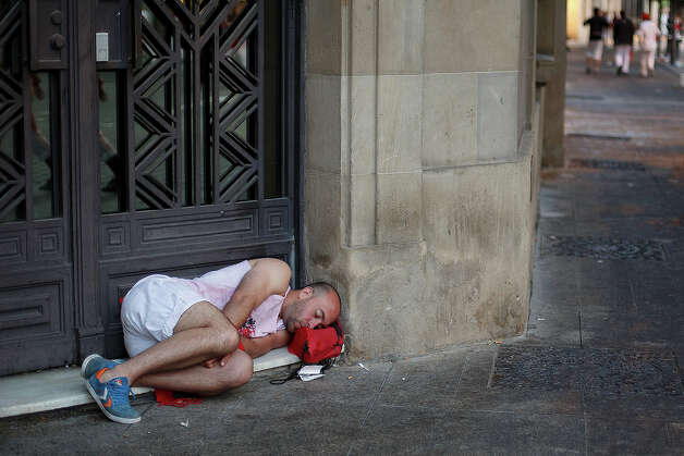 A reveller sleeps in the early hours ahead of the Alcurrucen's ranch fighting bulls running during the second day of the San Fermin Running Of The Bulls festival on July 7, 2013 in Pamplona, Spain. The annual Fiesta de San Fermin, made famous by the 1926 novel of US writer Ernest Hemmingway 'The Sun Also Rises', involves the running of the bulls through the historic heart of Pamplona, this year for nine days from July 6-14. Photo: Pablo Blazquez Dominguez, Getty Images / 2013 Getty Images