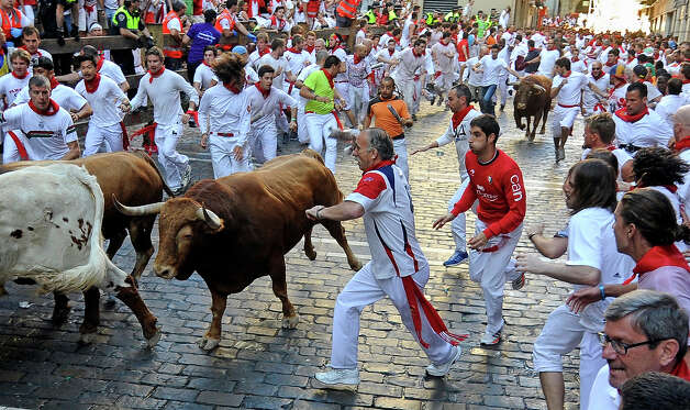 Participants run in front of Alcurrucen's bulls during the first bull run of the San Fermin Festival, on July 7, 2013, in Pamplona, northern Spain. The festival is a symbol of Spanish culture that attracts thousands of tourists to watch the bull runs despite heavy condemnation from animal rights groups. Photo: RAFA RIVAS, AFP/Getty Images / 2013 AFP