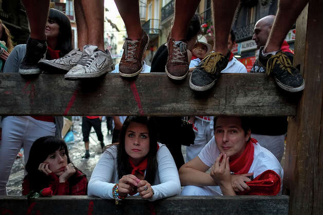 People watch the first bull run of the San Fermin Festival, on July 7, 2013, in Pamplona, northern Spain. The festival is a symbol of Spanish culture that attracts thousands of tourists to watch the bull runs despite heavy condemnation from animal rights groups. Photo: PEDRO ARMESTRE, AFP/Getty Images / 2013 AFP