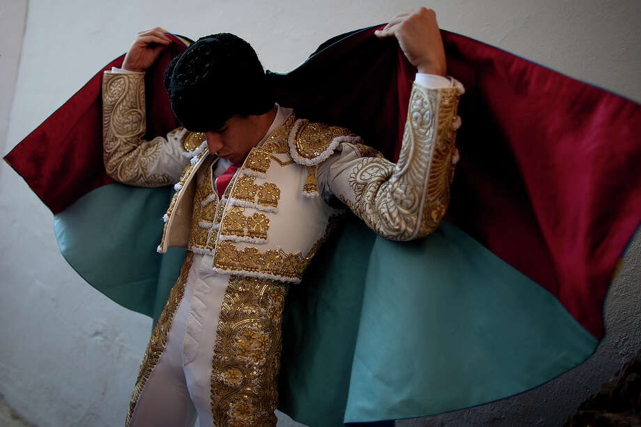 Bullfighter Alberto Lopez Simon puts on his capote before performing with Alcurrucen's fighting bulls in the bullring during the second day of the San Fermin Running Of The Bulls festival on July 7, 2013 in Pamplona, Spain. The annual Fiesta de San Fermin, made famous by the 1926 novel of US writer Ernest Hemmingway 'The Sun Also Rises', involves the running of the bulls through the historic heart of Pamplona, this year for nine days from July 6-14. Photo: Pablo Blazquez Dominguez, Getty Images / 2013 Getty Images