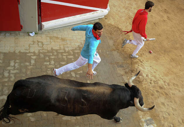 Participants run in front of Dolores Aguirre's bulls during a bull run of the San Fermin Festival in Pamplona, northern Spain, on July 8, 2013. The festival is a symbol of Spanish culture that attracts thousands of tourists to watch the bull runs despite heavy condemnation from animal rights groups. Photo: PEDRO ARMESTRE, AFP/Getty Images / 2013 AFP