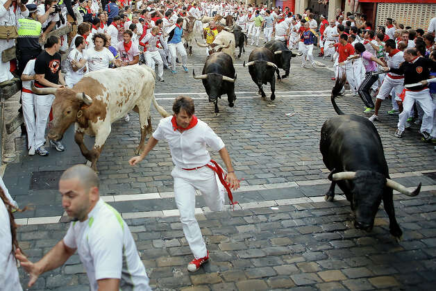 Revellers run with Dolores Aguirre's ranch fighting bulls at Curva Estafeta during the third day of the San Fermin Running Of The Bulls festival, on July 8, 2013 in Pamplona, Spain. The annual Fiesta de San Fermin, made famous by the 1926 novel of US writer Ernest Hemmingway 'The Sun Also Rises', involves the running of the bulls through the historic heart of Pamplona for nine days from July 6-14. Photo: Pablo Blazquez Dominguez, Getty Images / 2013 Getty Images