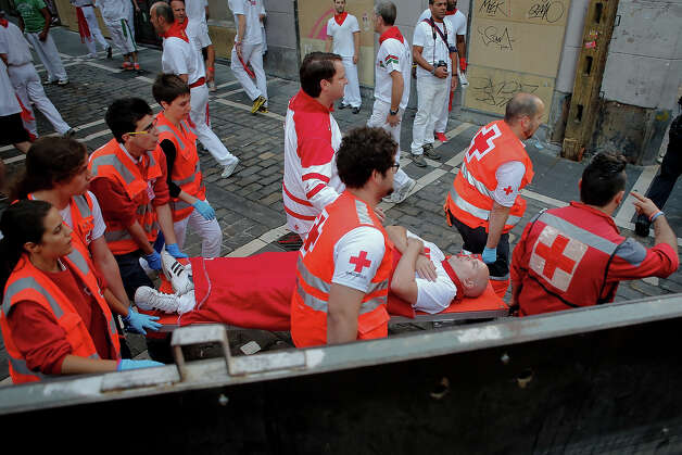 Medical services carry a man after Dolores Aguirre's ranch fighting bulls passed along Curva Estafeta during the third day of the San Fermin Running Of The Bulls festival, on July 8, 2013 in Pamplona, Spain. The annual Fiesta de San Fermin, made famous by the 1926 novel of US writer Ernest Hemmingway 'The Sun Also Rises', involves the running of the bulls through the historic heart of Pamplona for nine days from July 6-14. Photo: Pablo Blazquez Dominguez, Getty Images / 2013 Getty Images