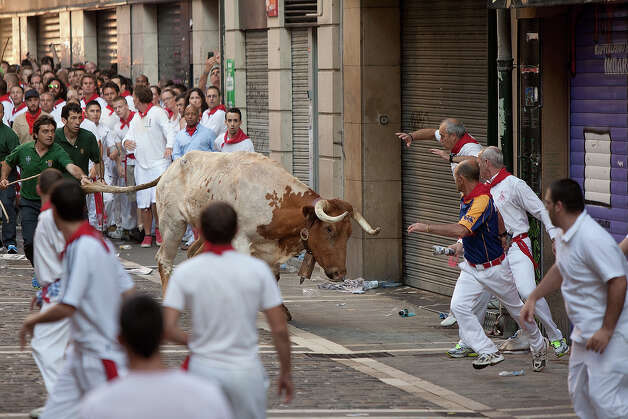 A steer runs towards revellers during the Dolores Aguirre's ranch fighting bulls running near Curva Estafeta on the third day of the San Fermin Running Of The Bulls festival, on July 8, 2013 in Pamplona, Spain. The annual Fiesta de San Fermin, made famous by the 1926 novel of US writer Ernest Hemmingway 'The Sun Also Rises', involves the running of the bulls through the historic heart of Pamplona for nine days from July 6-14. Photo: Pablo Blazquez Dominguez, Getty Images / 2013 Getty Images