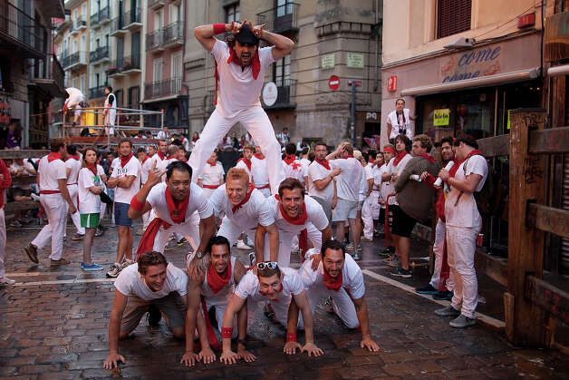 Revellers form a human tower to pose for a picture in the early hours ahead of Dolores Aguirre's ranch fighting bulls running on the third day of the San Fermin Running Of The Bulls festival, on July 8, 2013 in Pamplona, Spain. The annual Fiesta de San Fermin, made famous by the 1926 novel of US writer Ernest Hemmingway 'The Sun Also Rises', involves the running of the bulls through the historic heart of Pamplona for nine days from July 6-14. Photo: Pablo Blazquez Dominguez, Getty Images / 2013 Getty Images