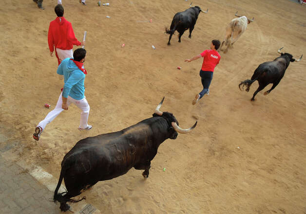 Participants run in front of Dolores Aguirre's bulls during the second bull run of the San Fermin Festival in Pamplona, northern Spain, on July 8, 2013. The festival is a symbol of Spanish culture that attracts thousands of tourists to watch the bull runs despite heavy condemnation from animal rights groups. Photo: PEDRO ARMESTRE, AFP/Getty Images / 2013 AFP