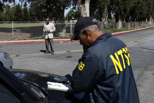 An NTSB officer talks on the phone while a United Airlines official turns cars away at the entrance of the Crowne Plaza where survivors of the plane crash are staying in Burlingame, Calif. on July 7, 2013. Photo: Ian C. Bates, The Chronicle