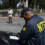An NTSB officer talks on the phone while a United Airlines official turns cars away at the entrance of the Crowne Plaza where survivors of the plane crash are staying in Burlingame, Calif. on July 7, 2013.