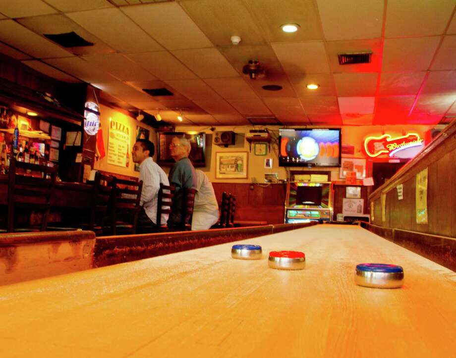 "Through the lens of Mike Harris' camera, the shuffle board table at Greenwich's Bruce Park Grill is momentarily quiet. This is one of many photographs that will be on display at the Greenwich (Conn.) Historical Society, beginning Wednesday, July 17, 2013. ""Greenwich: The Perspective of Time,"" is a collaboration between the historical society and the Stamford Photography Club. Club members were asked to find images that portrayed the history of Greenwich. The Bruce Park Grill is a longstanding neighborhood bar that many consider a town institution. It will be open Wednesday through Sunday, 12 to 4 p.m., 39 Strickland Road, Cos Cob. Photo: Contributed Photo / Stamford Advocate Contributed"