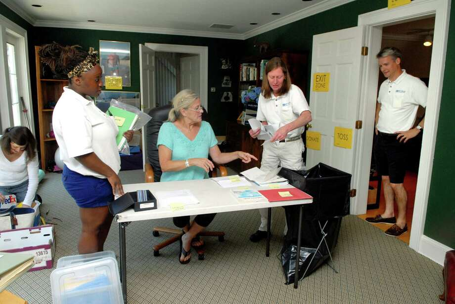 Matt Baier (in doorway) and his crew Linda Barlaam, Marlie Reid and Cathy Oakford sort thru items with homeowner Peggy Ogden (center) in New Canaan, Conn. on Monday July 8, 2013 in preparation for the house being put up for sale. Photo: Dru Nadler / Stamford Advocate Freelance