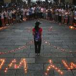 People gather to mourn for the two victims of the Asiana airline plane crash in San Francisco at a park in Jiangshan city in eastern China's Zhejiang province on Monday, July 8, 2013. Chinese state media and Asiana Airlines have identified the two victims of the Asiana Airlines crash at San Francisco International Airport girls as Ye Mengyuan and Wang Linjia, students in Zhejiang, an affluent coastal province in eastern China.