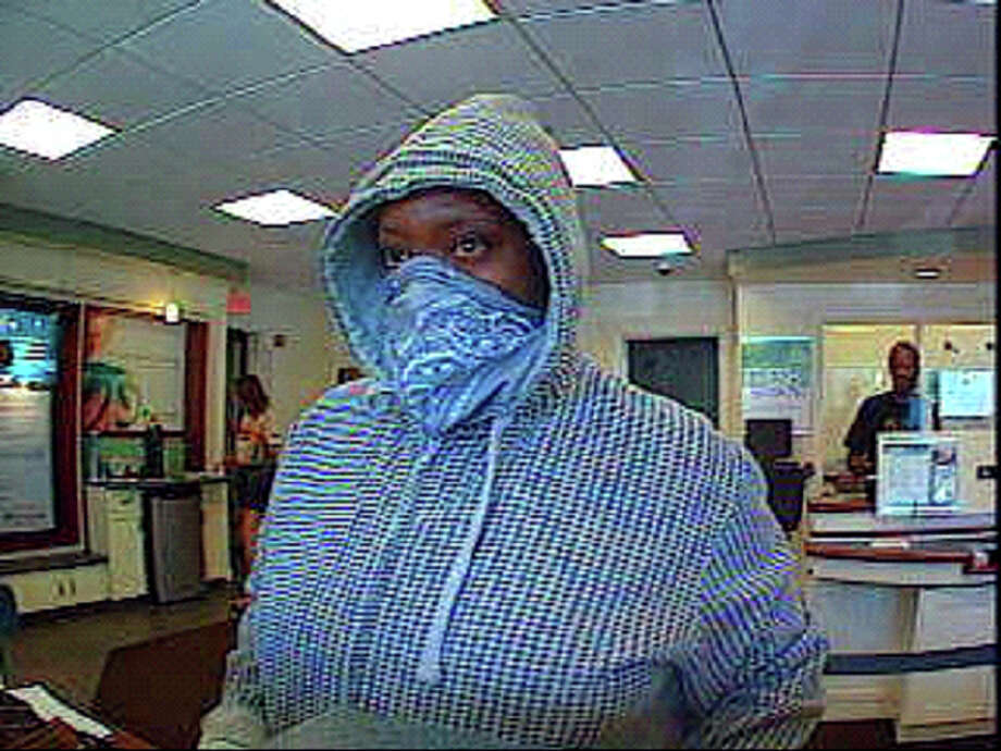 Police are seeking a woman who robbed First County Bank at 275 Hope Street on Monday July 8, 2013, wearing a bandanna and making off with an undetermined amount of cash. The robbery occurred at approximately 9:05 a.m. The woman was caught on security camera during the exchange with the teller. Photo: Contributed Photo / Stamford Advocate Contributed
