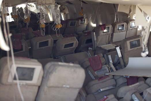 In this handout photo provided by the National Transportation Safety Board, oxygen masks hang from the ceiling in the cabin interior of Asiana Airlines flight 214 following yesterday's crash, on July 7, 2013 in San Francisco, California. The Boeing 777 passenger aircraft from Asiana Airlines coming from Seoul, South Korea crashed landed on the runway at San Francisco International Airport. Two people died and dozens were injured in the crash. Photo: Handout, Getty Images