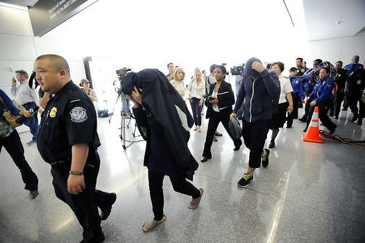 Potential victims of the Asiana plane crash cover their faces as they are lead by security out of the Reflection Room in the North Wing of the International Terminal at SFO in San Francisco, CA on July 6th, 2013. Photo: Michael Short, Special To The Chronicle