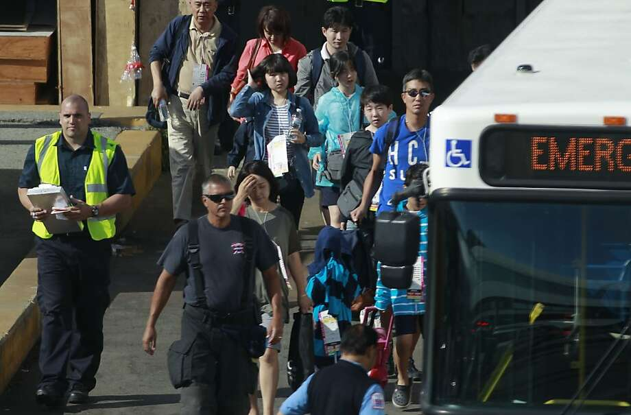 Emergency personnel assist passengers to transportation at the International terminal in San Francisco, Calif., on Saturday July 6, 2013, following the earlier crash of Asiana Airlines flight 214 at SFO. Photo: Michael Macor, The Chronicle