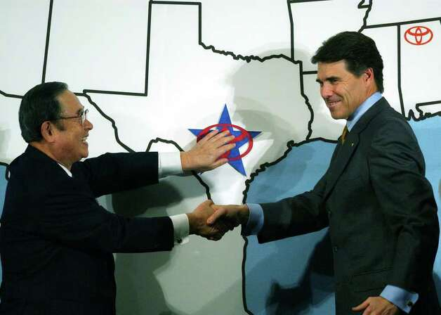 Toyota Motor Coporation President Fujio Cho, left, and Texas Gov. Rick Perry place a Toyota logo on San Antonio during a ceremony at the Institute of Texan Cultures, Feb. 10, 2003. Toyota will built the Tundra pickup truck at the San Antonio site.  Photo: JERRY LARA, SAN ANTONIO EXPRESS-NEWS / SAN ANTONIO EXPRESS-NEWS