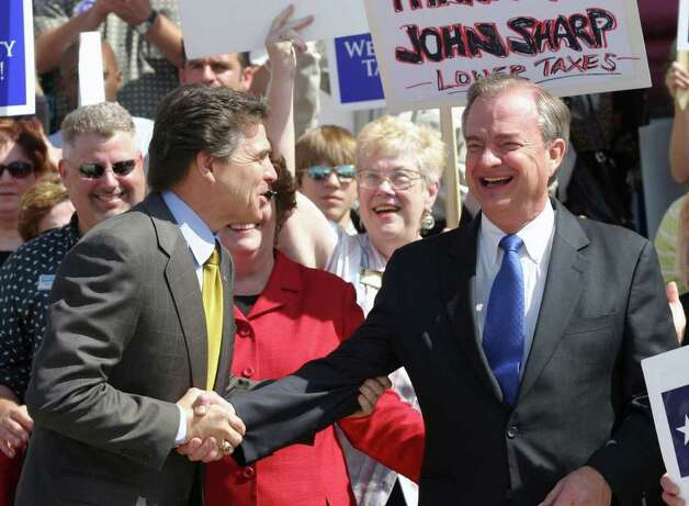 Gov. Rick Perry, left, greets former state comptroller John Sharp at a rally sponsored by the Texas Association of Realtors to show support for their joint property tax and school finance plan in Austin, April 17, 2006. Photo: JACK PLUNKETT, AP / AP