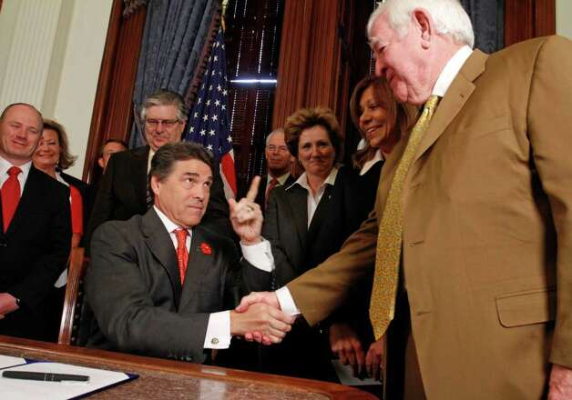 Texas Gov. Rick Perry shakes hands with Mike Gallager of Houston after signing a tort reform bill at the Capitol in Austin,  May 30, 2011.  Photo: AP