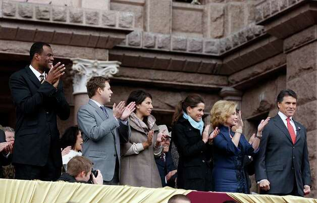Texas Governor Rick Perry receives applause as he is introduced during the 2011 Texas Inauguration Oath of Office Ceremony on the south steps of the Capitol in Austin, Jan. 18, 2011. It is Perry's fourth oath ceremony and Lt. Gov. David Dewhurst took the oath for a third term. With Perry on the stand are (from left) former San Antonio Spur David Robinson, Perry's son Griffin and wife Meredith Perry, daughter Sydney Perry and Anita, the first lady. Photo: JERRY LARA, San Antonio Express-News / glara@express-news.net