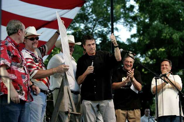 "Gov. Rick Perry gives a thumbs up to the crowd after signing the ""Contract with the Constitution,"" a document created by the San Antonio Tea Party and targeted toward public officials and centered around states' rights, at a Tea Party event in Marion, Texas, July 4, 2009. Photo: SHAMINDER DULAI, SAN ANTONIO EXPRESS-NEWS / sdulai@express-news.net"