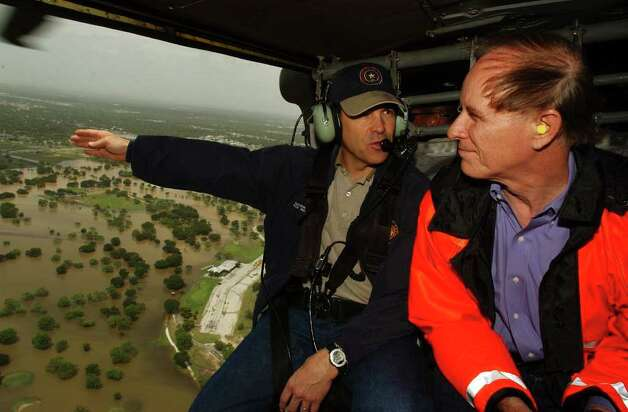 Gov. Rick Perry gestures to Bexar County Judge Nelson Wolff as they fly over flooded areas in a Texas Army National Guard Blackhawk helicopter, July 3, 2002.  Photo: BILLY CALZADA, SAN ANTONIO EXPRESS-NEWS / SAN ANTONIO EXPRESS-NEWS