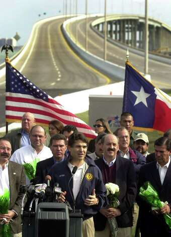 Gov. Rick Perry speaks at the reopening ceremony of the Queen Isabella Causeway at the Port Isabel foot of the structure on, Nov. 21, 2001. South Padre Island Mayor Ed Cyganiewicz and State Sen. Ed Lucio are to the right of Perry. The causeway was repaired just over two months after a string of barges hit and partially collapsed it, causing the deaths of eight people on Sept. 15, 2001. Photo: BILLY CALZADA, SAN ANTONIO EXPRESS-NEWS / SAN ANTONIO EXPRESS-NEWS